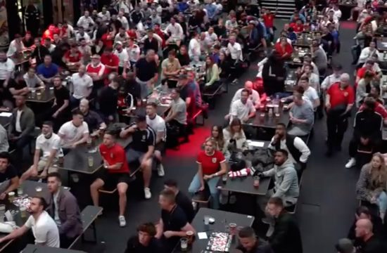 fans enjoying a drink as they watch